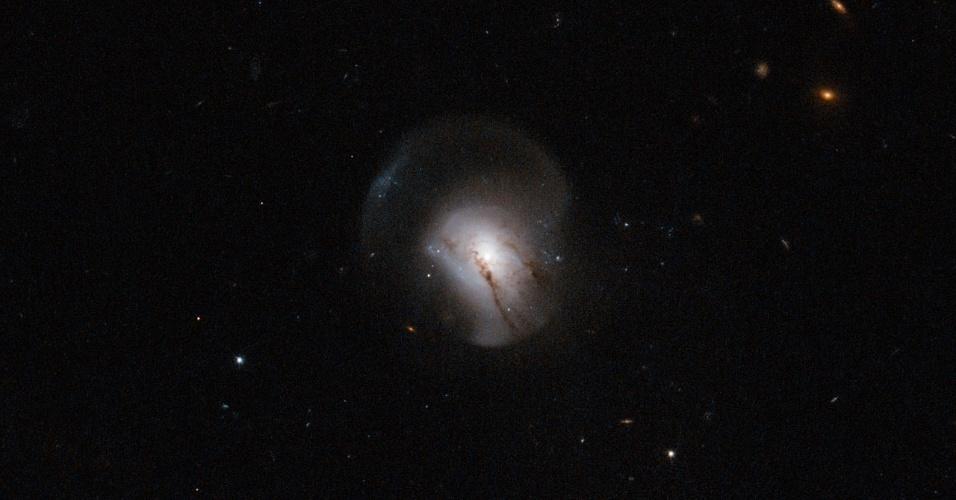 """4.fev.2013 - O telescópio Hubble detectou o momento que uma galáxia parou de criar estrelas, sugerindo que entrou na fase de transição para sua """"morte"""", abrigando apenas estrelas vermelhas e velhas. Segundo a Nasa (Agência Espacial Norte-Americana), a galáxia 2MASX J09442693+0429569 usou todo o gás, possivelmente, em uma fusão e, por isso, os astrônomos não conseguem encontrar mais sinais de estrelas jovens na região"""