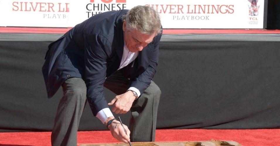 4.jan.2013 - O ator Robert de Niro deixa assinatura no cimento em frente ao Teatro Chinês, em Hollywood