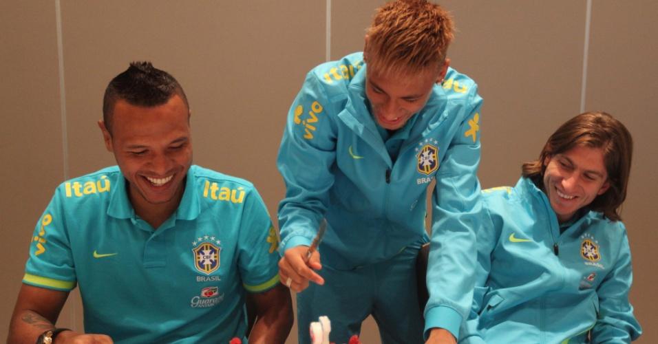 05.fev.2013 - Neymar oferece pedaço de bolo para Luís Fabiano e Filipe Luís em Londres, onde a seleção enfrenta a Inglaterra