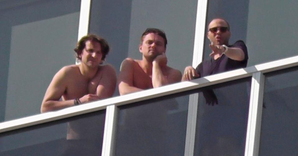 3.jan.2013 - Bradley Cooper e Leonardo DiCaprio apareceram na sacada do hotel onde ficaram hospedados em Miami, Flória, EUA. Os atores estavam acompanhados de mais um amigo