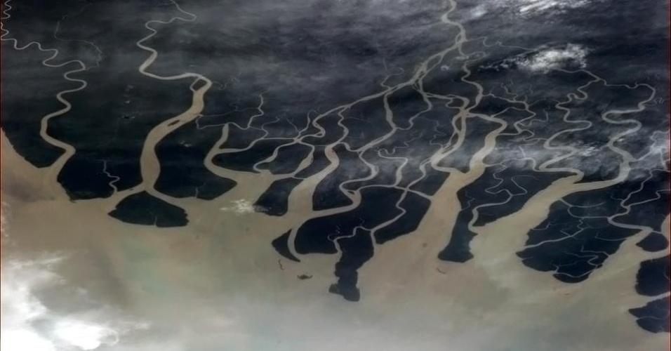 """5.fev.2013 - Em outro desafio, o astronauta canadense pergunta qual a melhor legenda para essa vista da Papua Nova Guiné. Os seguidores no Twitter deram respostas engraçadas, como: """"Derrubei terra no seu mar"""" e """"Papua: cobras no espaço"""""""