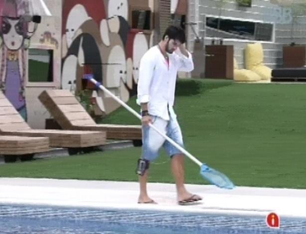 5.fev.2013 - Marcello limpa a piscina enquanto aguarda outros brothers acordarem