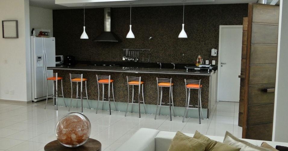 Banquetas coloridas e luminárias sobre o balcão deram vida à cozinha sóbria planejada pelo arquiteto Flavio Castro
