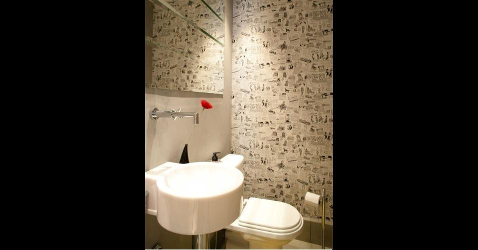Um papel de parede estampado com recortes de jornal foi aplicado neste lavabo projetado pelo arquiteto Henrique Machado