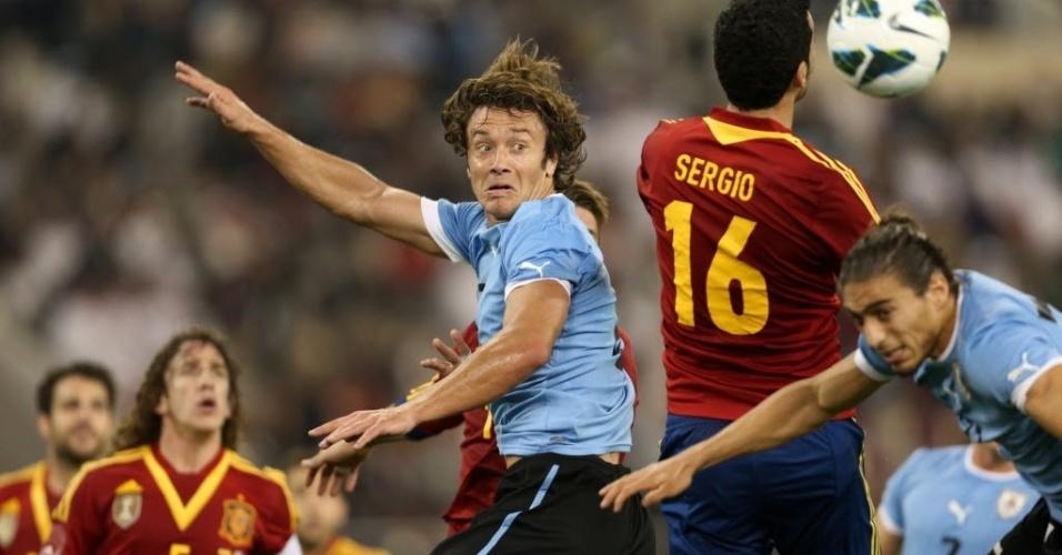 06.fev.2013 - Diego Lugano (centro), zagueiro uruguaio ex-São Paulo, disputa bola de cabeça no amistoso da sua seleção contra a Espanha