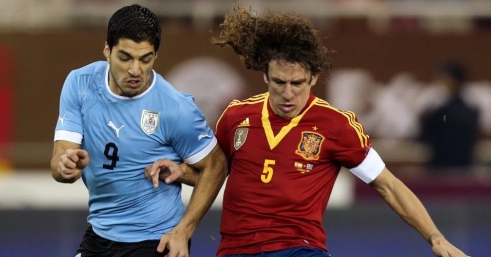 06.fev.2013 - Luis Suárez (esq.), atacante uruguaio do Liverpool, disputa o lance em amistoso pela sua seleção contra o zagueiro Puyol, da Espanha, nesta quarta-feira, em Doha, no Catar