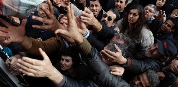 População se espreme para pegar frutas e vegetais distribuídos gratuitamente por agricultores durante protesto na Grécia