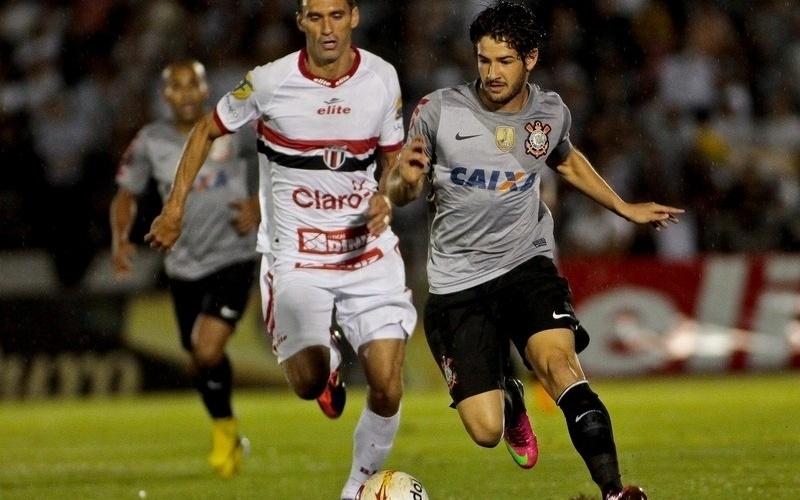 06.fev.2013 - Alexandre Pato, do Corinthians, disputa a bola com jogador do Botafogo-SP