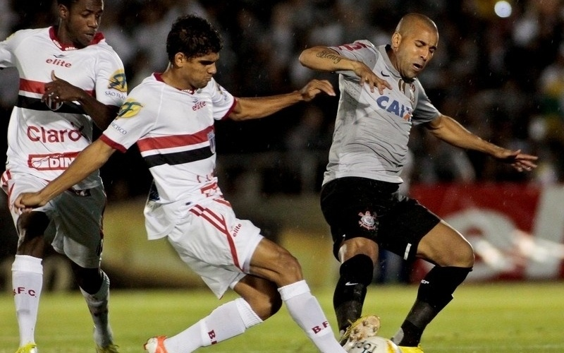 06.fev.2013 - Emerson Sheik, do Corinthians, disputa a jogada com defensores do Botafogo-SP