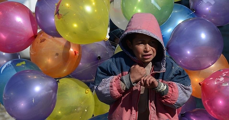 7.fev.2013 - Garoto afegão carrega balões para serem vendidos nas ruas de Cabul, nesta quinta-feira (7). O país enfrenta um dos invernos mais rigorosos dos últimos anos, e muitas pessoas dependem de ajuda humanitária para sobreviver às baixas temperaturas
