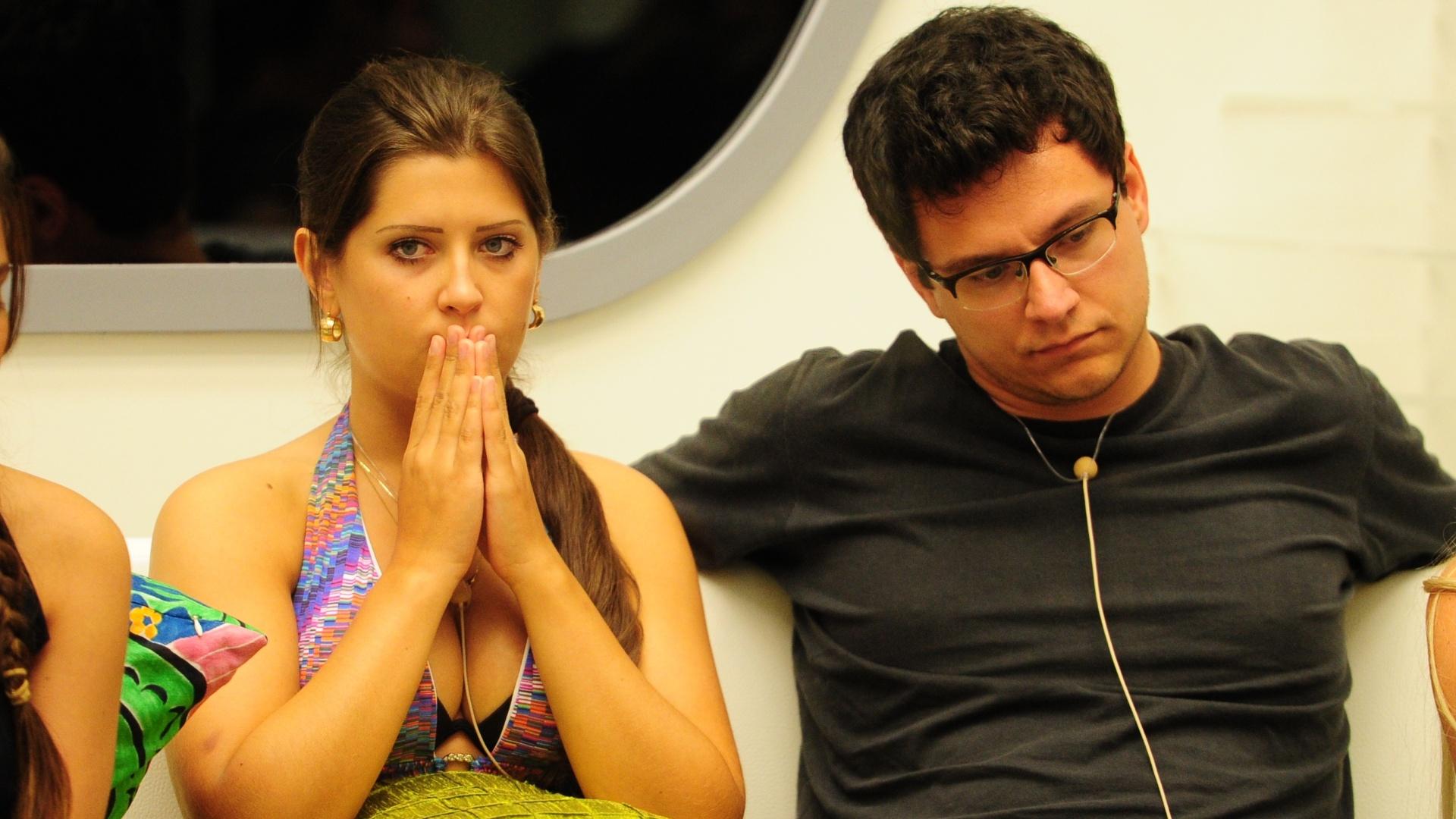 Andressa e Ivan sentam juntos no sofá da sala do