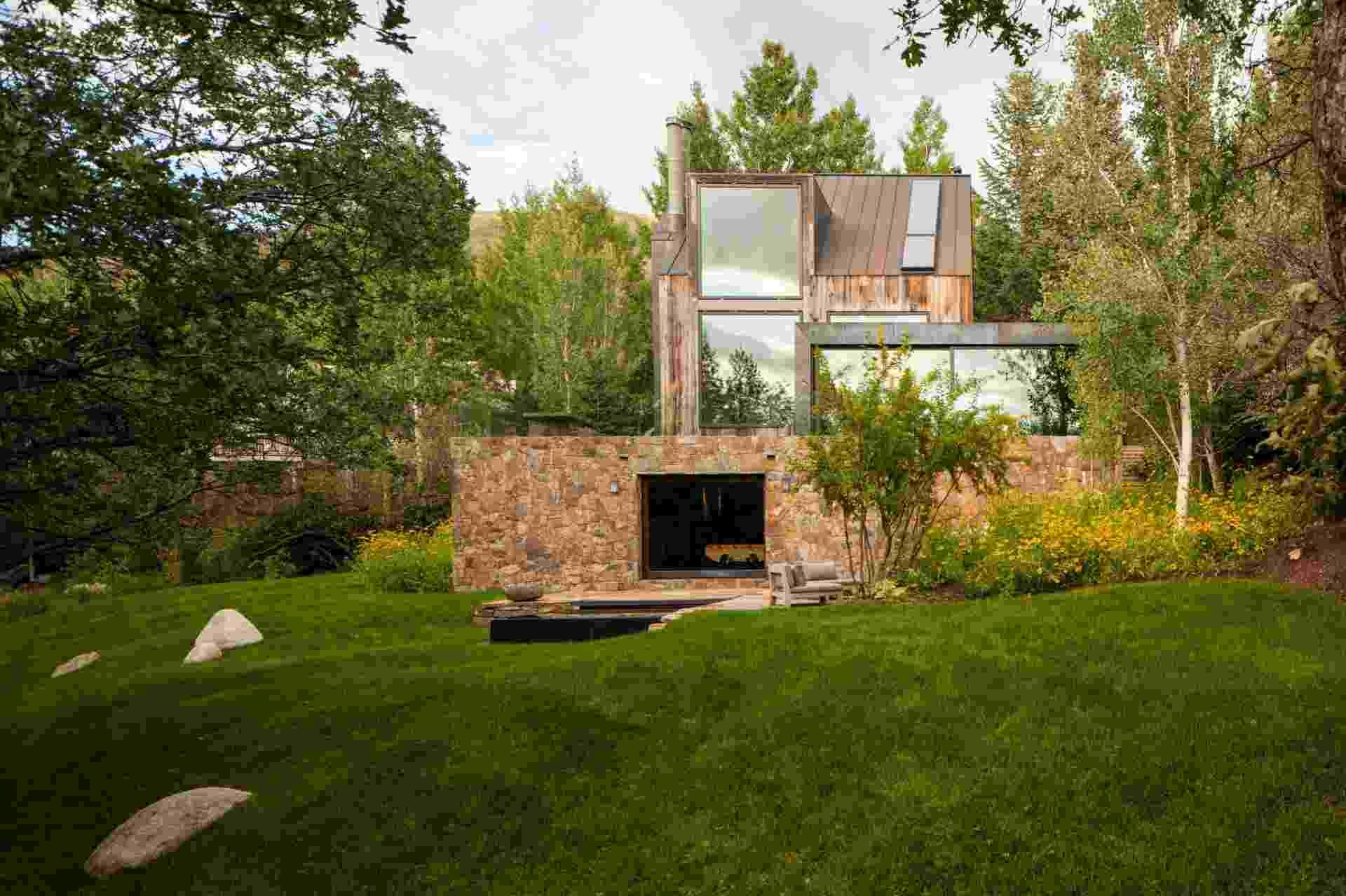 Em vez de competir com a paisagem, Chad Oppenheim projetou uma reforma para a casa construída nos anos 1970 que a fundisse e complementasse a natureza em redor. Assim, a construção foi revestida por pedras extraídas localmente, bem como por madeira, e ganhou amplos janelões de vidro  (Imagem do NYT, usar apenas no respectivo material) - Robert Reck/ The New York Times