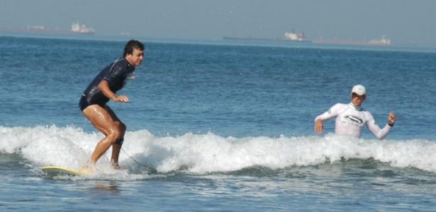 Valdemir Pereira Corrêa surfa com auxílio de seu professor Cisco Araña na Escola Radical, em Santos (SP) - Francisco Arrais/Divulgação Prefeitura de Santos