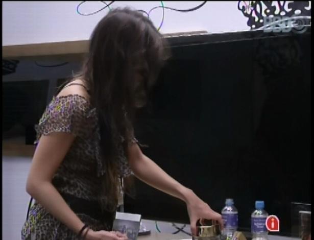 08.fev.2013 - Kamilla se levanta, pega alguns petiscos doces e salgados e começa a comer.