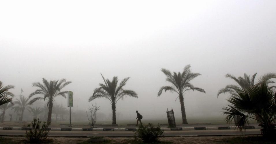 10.fev.2013 - Estudante palestino caminha em rua de Gaza, em meio a névoa que paira sobre a cidade