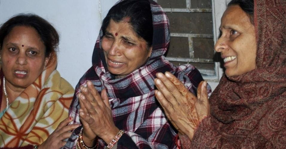 Mulheres choram por seus parentes mortos em um incidente na estação de trem de Allahabad, na Índia