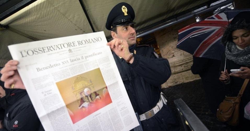 11.fev.2013 - Policial exibe cópia do jornal vaticano