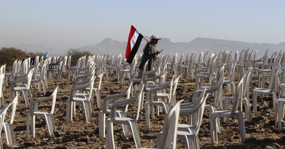11.fev.2013 - Rebelde carrega bandeira do Iêmen entre cadeiras que foram usadas em comício na cidade de Bani Hushaish