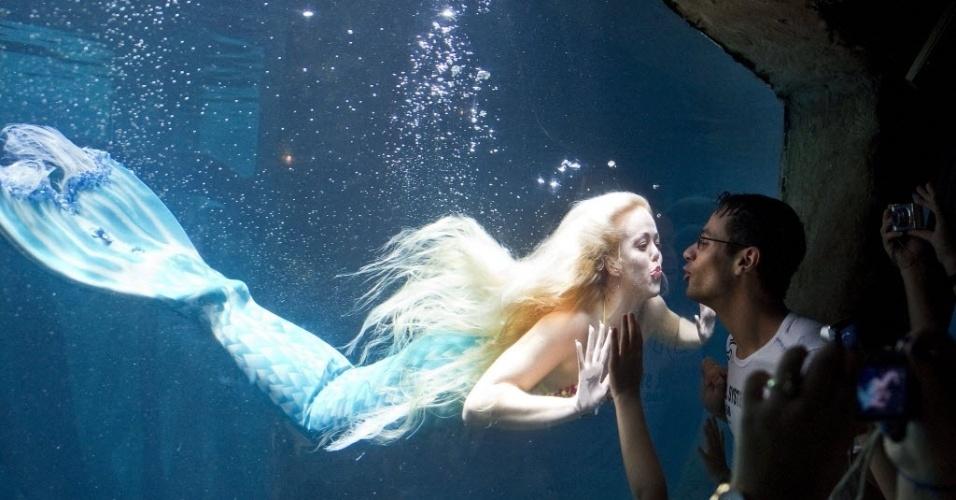 """11.fev.2013 - Visitante beija vidro próximo a Mirella Ferraz, apelidada como """"a sereia brasileira"""", enquanto ela nada em aquário em São Paulo"""