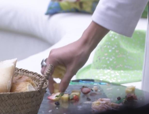 12.fev.2013 - A líder Kamilla pega os restos da comida que sobrou da noite anterior