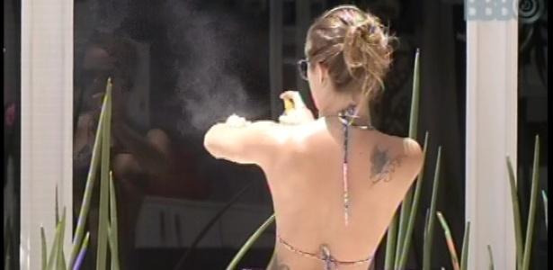 12.fev.2013 - Já na piscina, Natália passa protetor solar no corpo