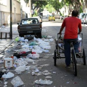 Ciclista desvia de lixo no centro do Rio de Janeiro na Quarta-feira de Cinzas, após a passagem de dezenas de blocos de rua pela cidade