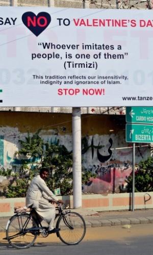 """13.fev.2013 - Homem passa diante de outdoor onde se lê """"Diga não ao Valentine´s Day - Aquele que imita um povo pertence a ele"""", em Karachi, no Paquistão, nesta quarta-feira (13). Comemorado no dia 14 de fevereiro nos Estados Unidos e em países da Europa, o Valentine's Day --Dia dos Namorados-- é cada vez mais popular entre os jovens paquistaneses"""