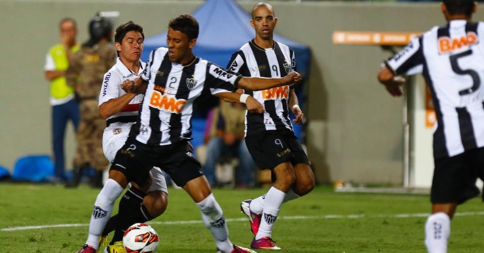 13.fev.2013 - Marcos Rocha, do Atlético-MG, e Osvaldo, do São Paulo, dividem a bola
