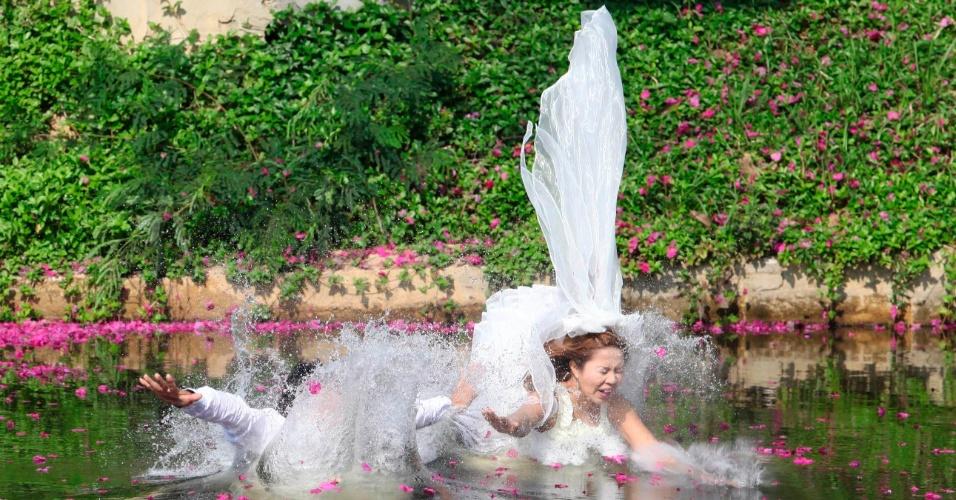 13.fev.2013 - Noivos saltam em um lago durante cerimônia de casamento em Prachin Buri, na Tailândia