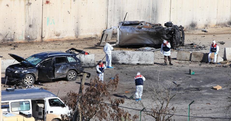 13.fev.2013 - Policiais turcos limpam local onde um carro-bomba explodiu na segunda-feira (11) em Cilvegozu, na fronteira com a Síria. O atentado deixou 14 mortos