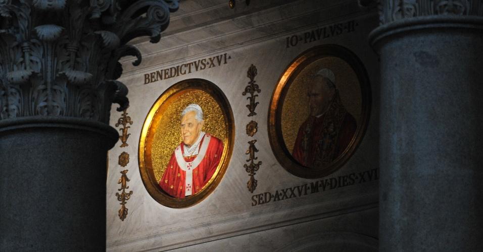 13.fev.2013 - Retrato do papa Bento 16 é exibido ao lado do retrato do papa João Paulo 2º em uma das paredes da Basílica de São Pedro, no Vaticano