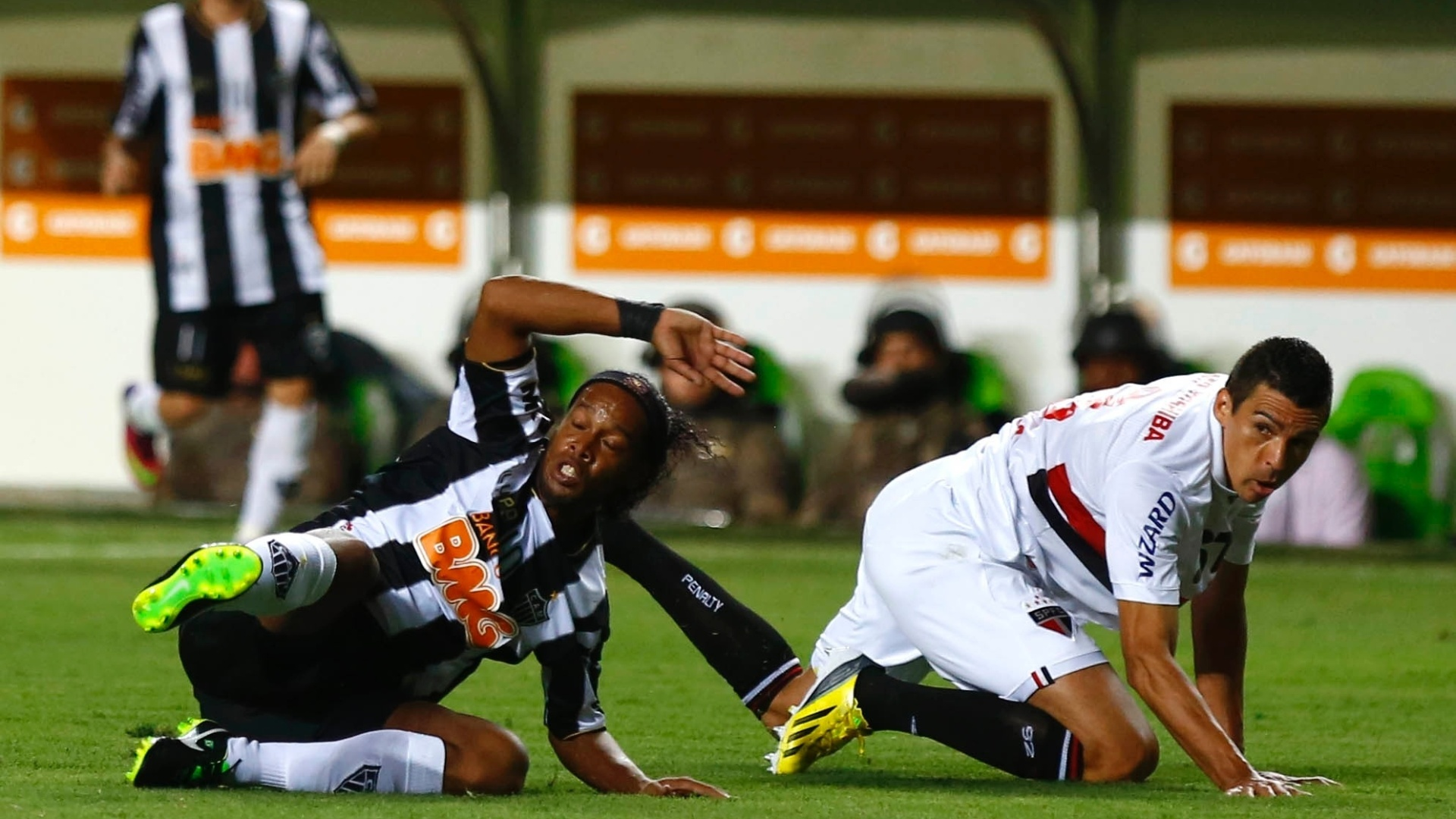 13.fev.2013 - Ronaldinho Gaúcho, do Atlético-MG, e Lúcio, do São Paulo, vão ao chão