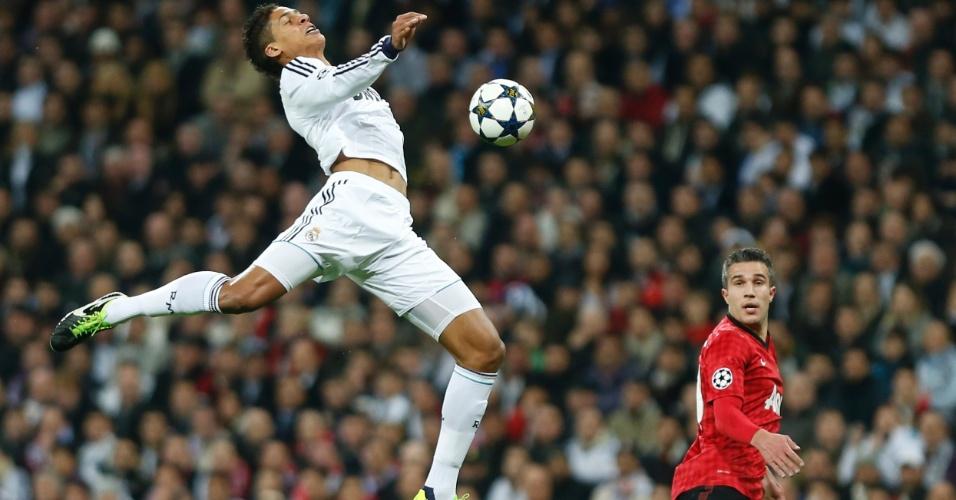 13.fev.2013- Observado por Van Persie, Raphael Varane, do Real Madrid, salta para chutar a bola durante duelo pelas oitavas da Liga dos Campeões