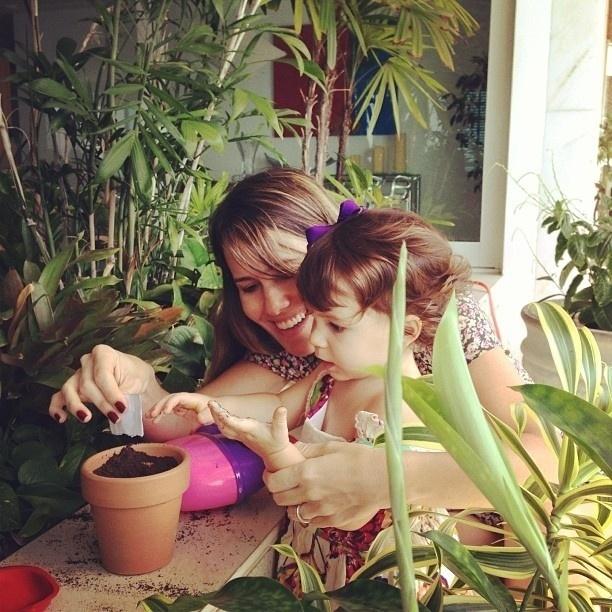 14.fev.2013 - Fernanda Pontes ensina a filha a plantar