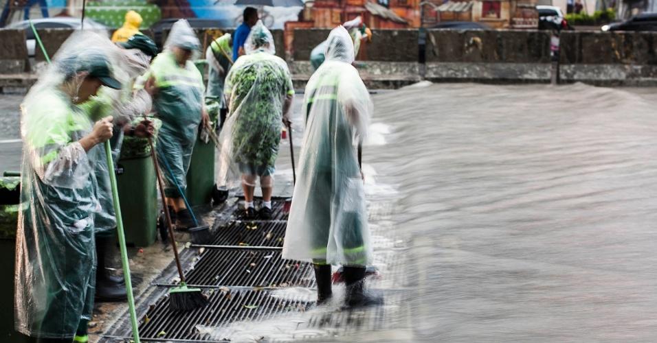 14.fev.2013 - Garis trabalham em meio a alagamento próximo ao terminal Bandeira, no Anhangabaú, região central de São Paulo, após o forte temporal que atingiu a cidade nesta quinta-feira (14)