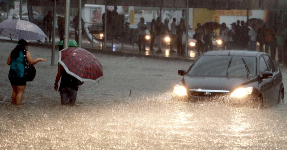 14.fev.2013 - Pessoas caminham com água na altura dos joelhos no cruzamento das avenidas Brigadeiro Faria Lima e Rebouças, em Pinheiros (zona oeste de São Paulo), durante temporal que atinge a cidade nesta quinta-feira (14)