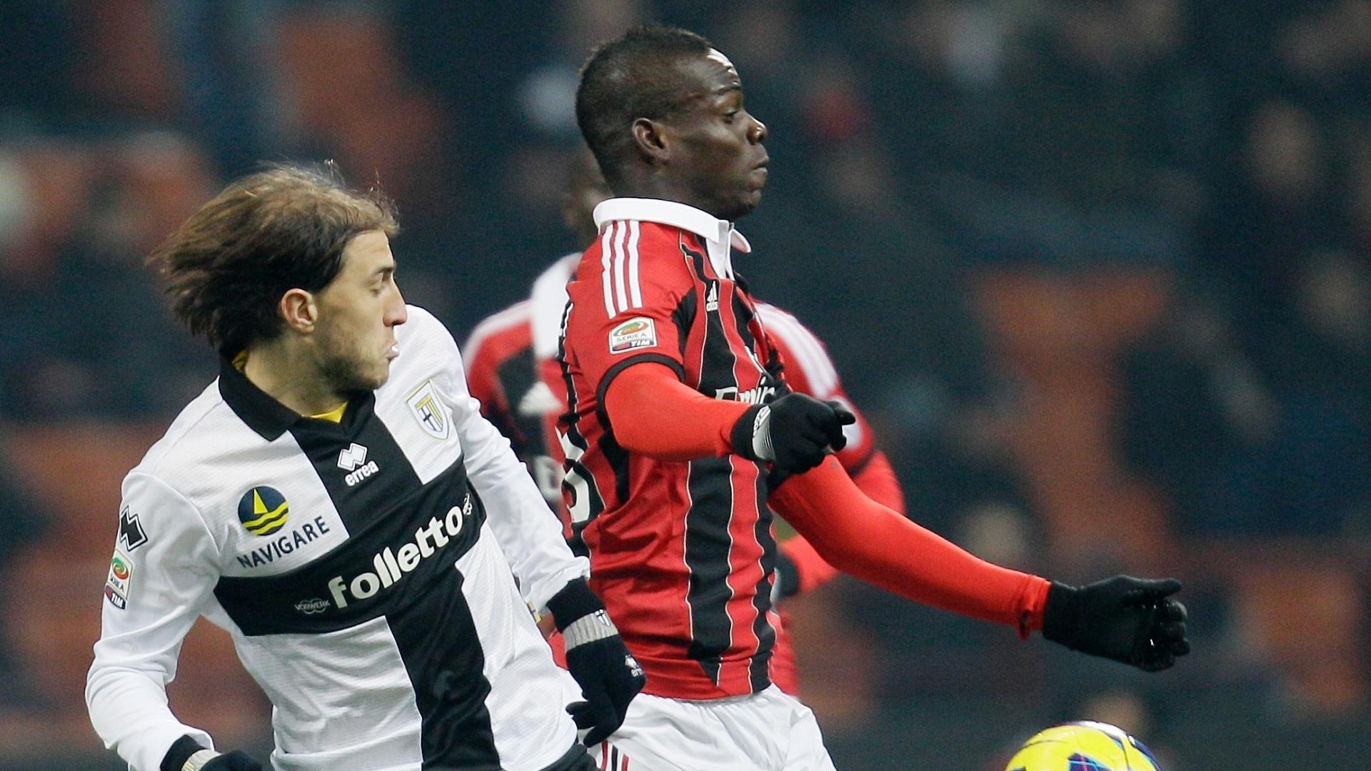 15.fev.2013 - Mario Balotell (dir.) do Milan, leva tranco do argentino Gabriel Paletta, do Parma, em, jogo do Campeonato Italiano