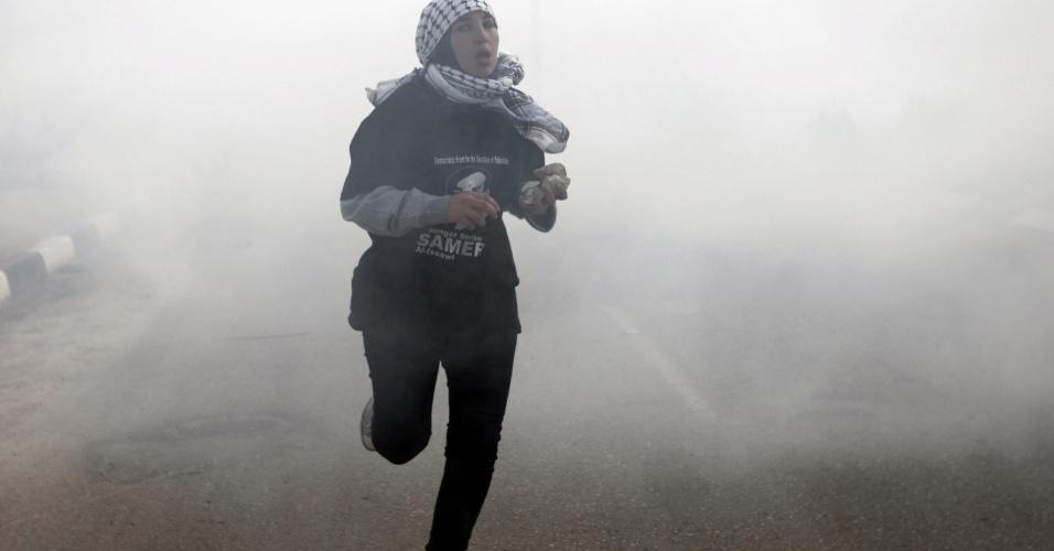 15.fev.2013 - Mulher palestina corre após lançamento de gás lacrimogêneo durante uma manifestação em apoio aos palestinos presos em Israel, ao sul de Ramalla, na Cisjordânia