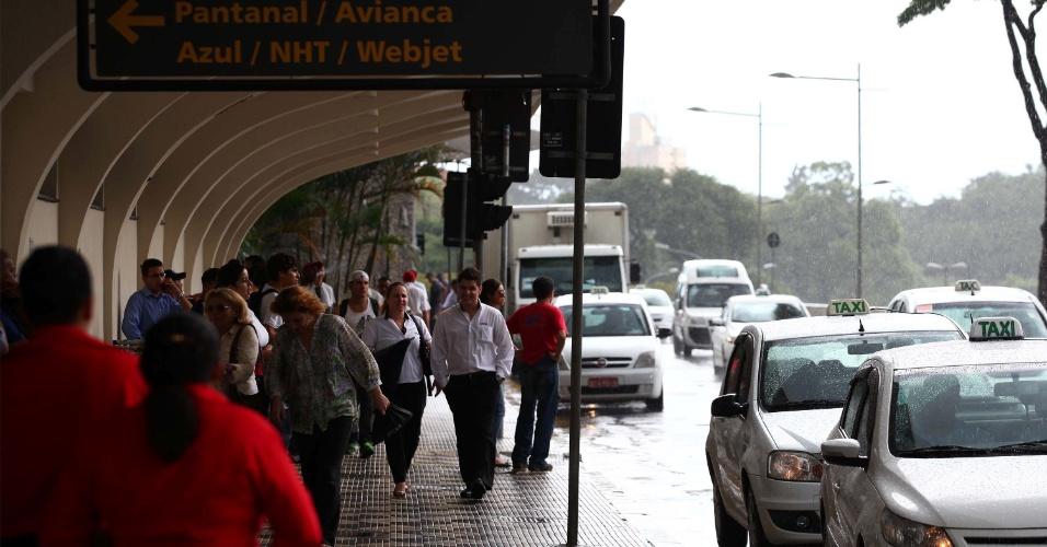 15.fev.2013 - Passageiros que desembarcaram no aeroporto de Congonhas se protegem da chuva na tarde desta sexta-feira (15) em São Paulo (SP)
