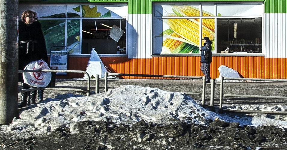 15.fev.2013 - Pessoas aparecem em frente a fachada de uma loja local que foi danificada pela onda de choque provocada pela passagem de um meteoro em  Tcheliabinsk, Rússia. Quase mil pessoas ficaram feridas