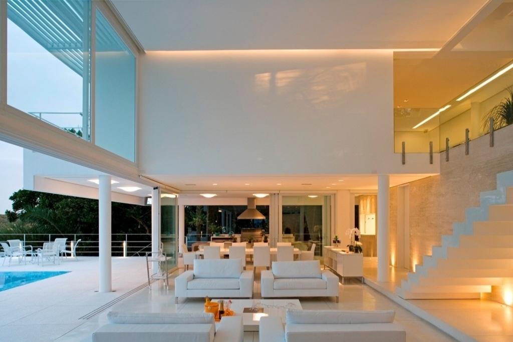 A sala de estar é totalmente integrada ao exterior, assim como aos espaços de jantar e à varanda com churrasqueira. Destaque para a parede revestida em mármore travertino navona que se diferencia do restante dos revestimentos, todos brancos, como o piso de granilite. A residência Iporanga foi projetada pelos profissionais do escritório Ximenes Leite Arquitetura em parceria com o arquiteto Mario Biselli