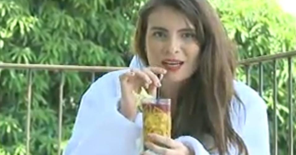 """16.fev.2013 - Kamilla bebe drink na varanda de hotel e fala para a câmera que voltará """"insuportável"""" para a casa"""