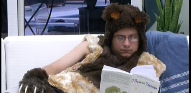 16.fev.2013 - Vestido de ursinho, cumprindo o castigo do anjo, e sem poder nadar na piscina, Ivan lê o livro