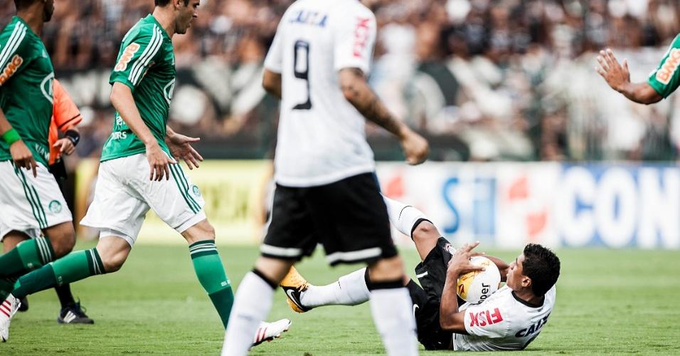 17.fev.2013- Paulinho segura a bola após sofrer falta e cair no gramado do Pacaembu durante clássico com o Palmeiras