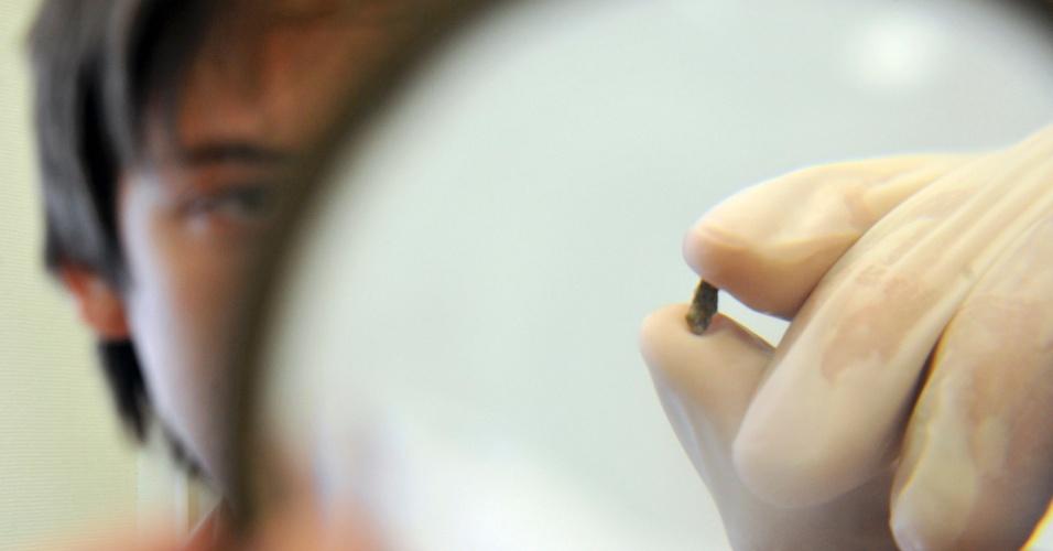 18.fev.2013 - Pesquisador da Universidade Federal dos Urais, na Rússia, examina fragmento do meteorito que foi encontrado ao redor do lago Chebarkul, na região de Tcheliabinsk. Segundo a Universidade, o material encontrado contém cerca de 10% de ferro