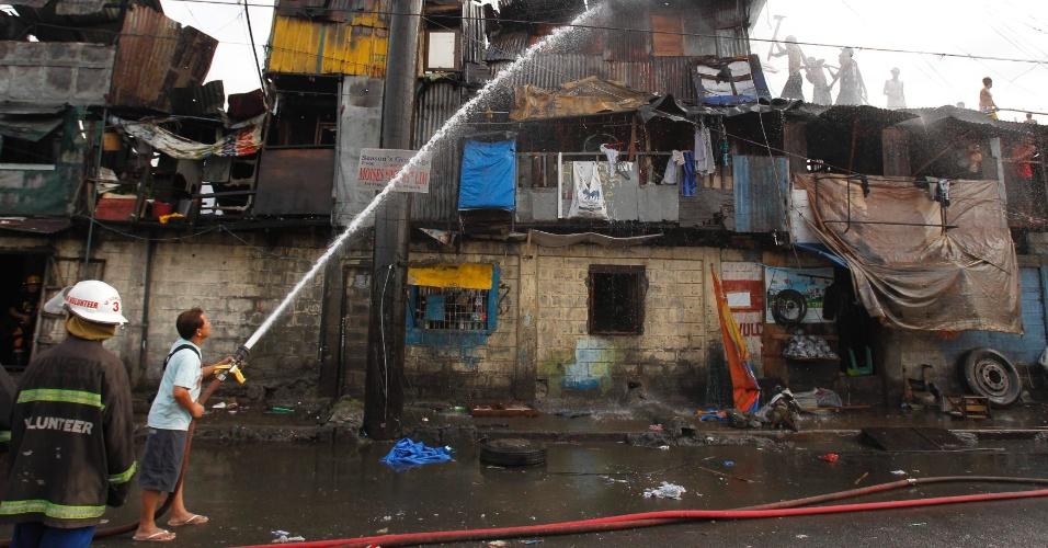 19.fev.2013 - Bombeiros e moradores tentam apagar incêndio em favela na cidade de Tondo, nas Filipinas. Pelo menos três pessoas morreram, segundo a imprensa local