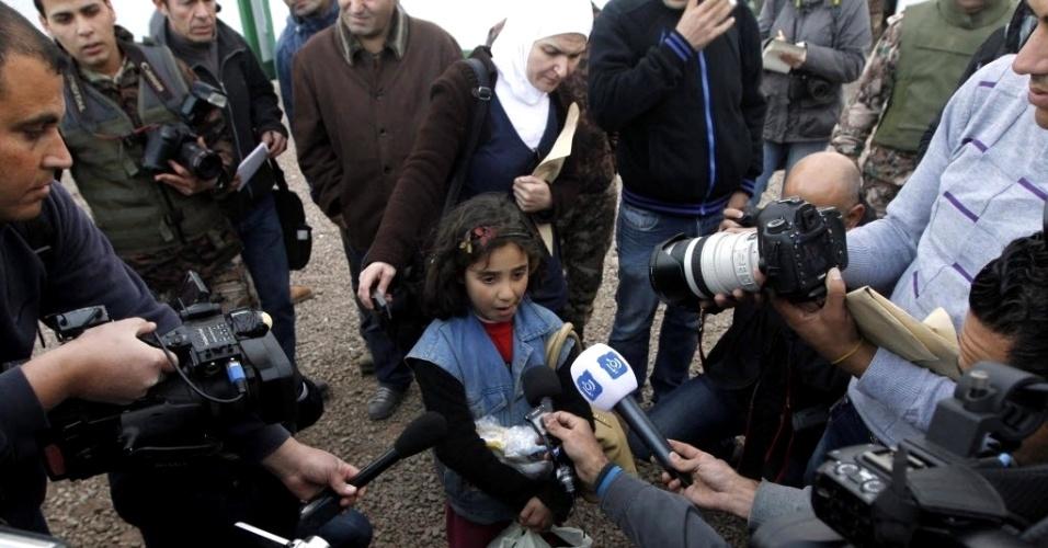 19.fev.2013 - Menina refugiada síria é entrevistada por jornalistas ao chegar a Mafraq (Jordânia). De acordo com as Forças Armadas do país, cerca de 2.500 refugiados sírios fogem todos os dias em direção à Jordânia e um total de 56 mil chegaram ao país apenas no mês de janeiro deste mês