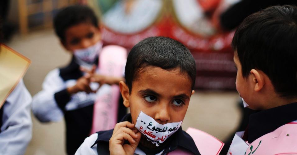 """19.fev.2013 - Menino palestino cobre sua boca com um adesivo (""""Sim à fome, não ao rebaixamento), durante um protesto para mostrar solidariedade com os prisioneiros palestinos em greve de fome em prisões israelenses, na Cidade de Gaza"""