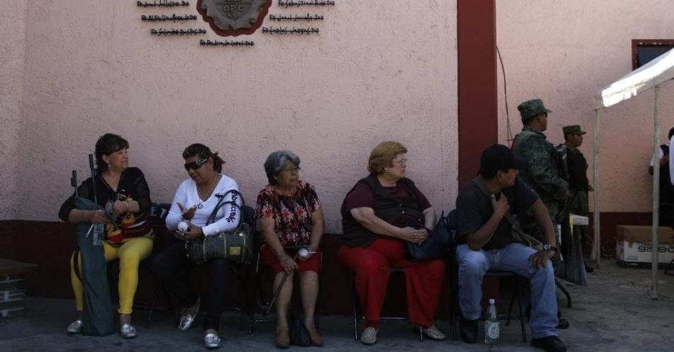 """19.fev.2013 - Mexicanos aguardam em fila sua vez de participar do """"Programa Voluntário de Desarmamento"""", desenvolvido pelo governo da Cidade do México com o apoio do Exército e da Igreja Católica. As armas são trocadas por dinheiro ou por um tablet"""