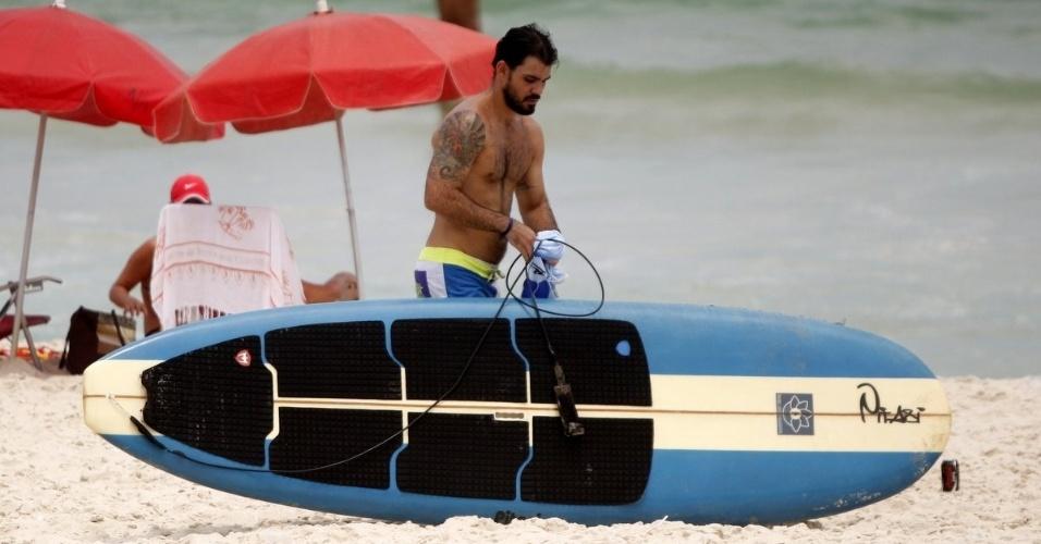 19.fev.2013 - O ator Juliano Cazarré prepara prancha antes de praticar stand-up paddle na praia da Barra da Tijuca